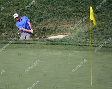 Hunter Mahan hits to the 12th green during the first round of the Memorial golf tournament, in Dublin, Ohio