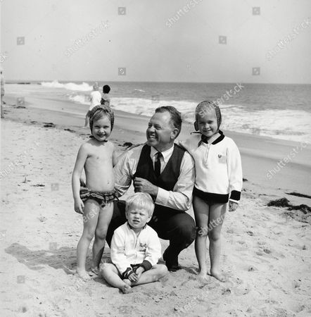 Stock Image of Actor Mickey Rooney is pictured with his children at a beach location in this undated photograph. From left are: daughter Kerry, 4, son Kyle, 3, and 5-year-old daughter Kelly, 5