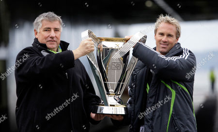 Sigi Schmid, Chris Henderson Shows Seattle Sounders coach Sigi Schmid, left, and MLS player Chris Henderson carrying the Major League Soccer championship trophy during the arrival of the cup in Seattle. The Seattle Sounders and Schmid are parting ways after eight years. The team announced, that Schmid's run as the only coach in the franchise's MLS era is coming to an end. Longtime Sounders assistant Brian Schmetzer is immediately taking over as interim head coach