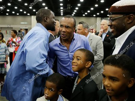 Former boxing champion Sugar Ray Leonard, center, is greeted by former two time heavyweight world champion Hasim Rahman before Muhammad Ali's Jenazah, a traditional Islamic Muslim service, in Freedom Hall, in Louisville, Ky