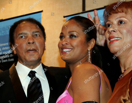 """Former heavyweight boxing champion Muhammad Ali, left, jokingly holds up two fingers behind the head of his daughter, Laila Ali, as they and his wife, Lonnie Ali, pose for cameras during a news conference before a tribute to him coinciding with Black History Month in Atlanta. Laila Ali told NBC's """"Today"""" show on that her father is not suffering anymore. Muhammad Ali died Friday at 74 following a long battle with Parkinson's disease"""