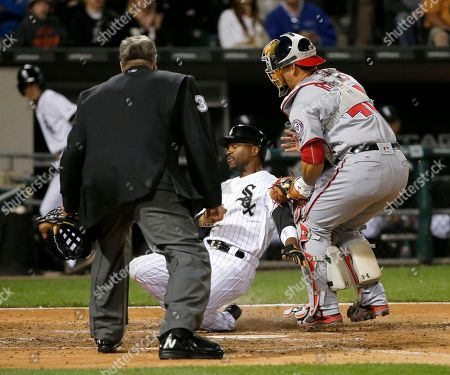 Eric Cooper, Jimmy Rollins, Wilson Ramos Washington Nationals catcher Wilson Ramos, right, tags out Chicago White Sox's Jimmy Rollins at home off a throw from right fielder Bryce Harper, as home plate umpire Eric Cooper watches during the fifth inning of a baseball game, in Chicago