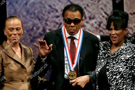 Retired boxing champion Muhammad Ali, center, waves alongside his wife Lonnie Ali, left, and his sister-in-law Marilyn Williams, right, after receiving the Liberty Medal during a ceremony at the National Constitution Center in Philadelphia. Ali, the magnificent heavyweight champion whose fast fists and irrepressible personality transcended sports and captivated the world, has died according to a statement released by his family . He was 74
