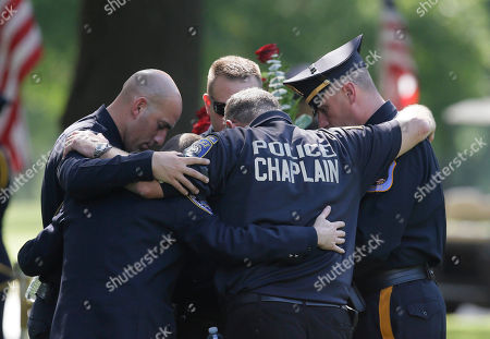 Law enforcement officers embrace each other as they pray after the graveside service for Dallas Police Sgt. Michael J. Smith at Restland Funeral Home and Cemetery in Dallas, . Smith was one of five police officers killed during a protest in Dallas the previous week