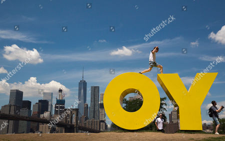 Stock Photo of A visitor to the Brooklyn Bridge park jumps between the letters in Deborah Kass' sculpture OY/YO in New York on