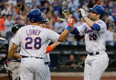 New York Mets' Neil Walker (20) is greeted at home plate by James Loney (28) and Michael Conforto after hitting a two-run home run against the Chicago White Sox during the third inning of a baseball game, in New York