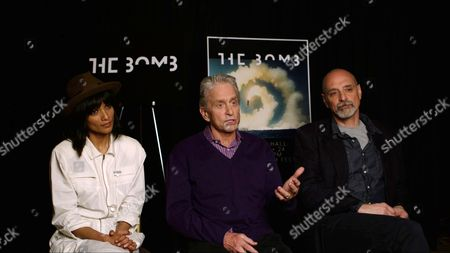 """In this image made from video, Michael Douglas, center, sits with filmmakers Smriti Keshari, left, and Eric Schlosser, in New York. Their groundbreaking multimedia installation on the threat of nuclear war, """"The Bomb,"""" will close the Tribeca Film Festival. Douglas wore purple to honor the late music icon, Prince"""