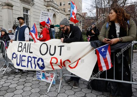 Protesters express their opposition to the fact the the Federal Reserve bank bailed out Wall Street but not Puerto Rico outside International House, in New York, where Federal Reserve chair Janet Yellen appeared with former Federal Reserve chairs Ben Bernanke, Paul Volcker and Alan Greenspan, who appeared via video conference