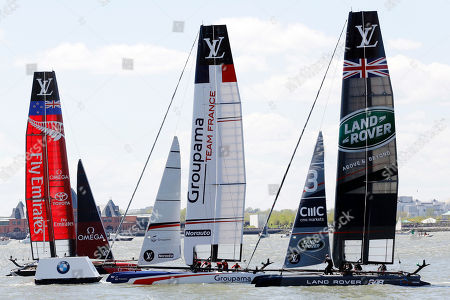 Emirates Team New Zealand, left, Team France, center, and Ben Ainslie Racing of Great Britain round a mark during an America's Cup sailing event, on the Hudson River in New York