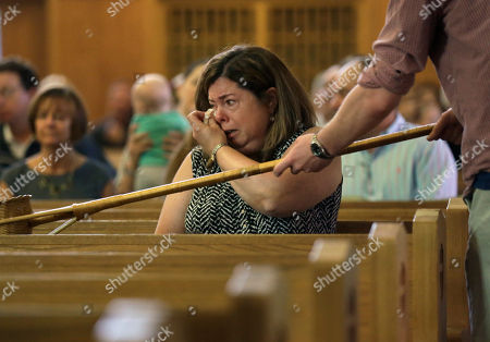Parishioner Christine Kane, of Pembroke, Mass., center, is tearful during a planned final service at St. Frances X. Cabrini Church, in Scituate. For more than 11 years, a core group of about 100 die-hard parishioners at the church have kept their parish open by maintaining an around-the-clock vigil in protest of a decision by the Roman Catholic Archdiocese of Boston to close it following the clergy sex abuse crisis