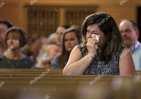 Parishioner Christine Kane, of Pembroke, Mass., front, cries during a planned final service at St. Frances X. Cabrini Church, in Scituate. For more than 11 years, a core group of about 100 die-hard parishioners at the church have kept their parish open by maintaining an around-the-clock vigil in protest of a decision by the Roman Catholic Archdiocese of Boston to close it following the clergy sex abuse crisis