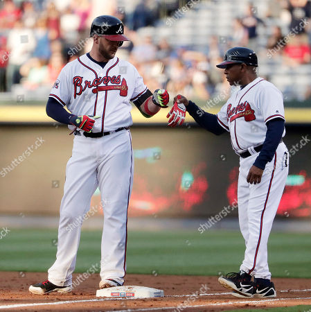 Stock Image of Tyler Flowers, Terry Pendleton Atlanta Braves' Tyler Flowers, left, fist-bumps first base coach Terry Pendleton after hitting single to score Freddie Freeman during the first inning of a baseball game against the Los Angeles Dodgers, in Atlanta