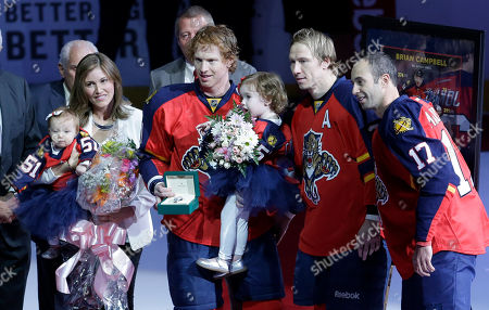 Brian Campbell, Lauren Miller, Derek MacKenzie, Jussi Jokinen Florida Panthers defenseman Brian Campbell, second from left, poses for photos with his wife Lauren Miller, left, his two young daughters, teammates Derek MacKenzie (17) and Jussi Jokinen, second from right, before an NHL hockey game, in Sunrise, Fla. Campbell's teammates presented him with a Rolex watch for playing his 1,000 game last Thursday in a special ceremony