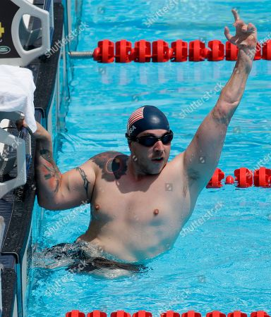 Tim Payne celebrates his victory in the men's 100 meter LC freestyle ISC race during the swimming events at the Invictus Games, in Kissimmee, Fla