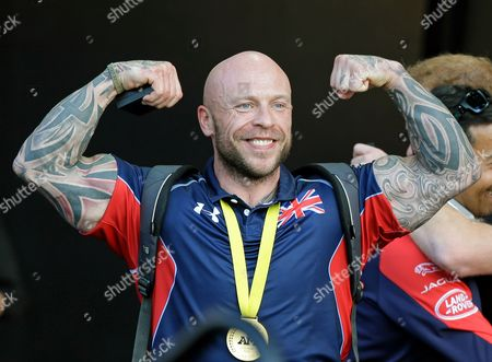Michael Yule, of the United Kingdom, flexes after being greeted by Prince Harry during the closing ceremony at the Invictus Games, in Kissimmee, Fla