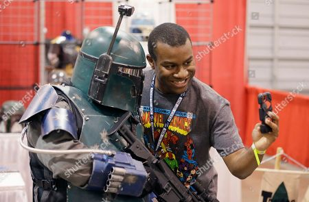 Stock Photo of Christopher Parker takes a selfie with a Boba Fett character at the Motor City Comic Con, in Novi, Mich. Tens of thousands of fans are expected at the 27th annual convention which got underway Friday. The three-day pop-culture extravaganza welcomes dozens of celebrities from TV and film as well as hundreds of comic book creators, writers and artists