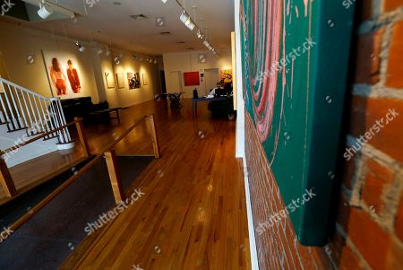 Artwork, left, by painter Tom Dash, depicting a partially a nude woman, hangs at Borghi Fine Art Gallery in Englewood, N.J., . The gallery has filed a federal lawsuit arguing that its constitutional rights were violated when it was fined $1,250 per day and the owner, Laura Borghi, was threatened with up to 90 days in jail over the artwork, which shows a woman's bare buttocks. A city code says nude images have to be kept in interior rooms not visible from public areas