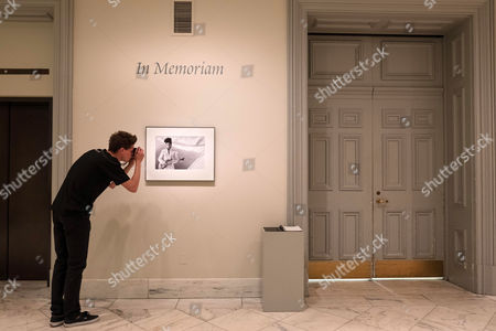 Stock Image of A visitor to the National Portrait Gallery in Washington stops to take a picture of the Lynn Goldsmith portrait of Prince hanging in memoriam in the museum, . The acclaimed musician was found dead at his home yesterday in suburban Minneapolis
