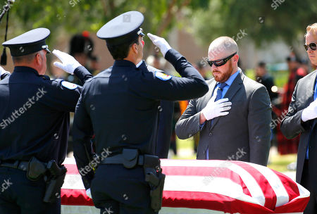 Pallbearers salute during the funeral for Phoenix Police Officer David Glasser, in Phoenix. Officer Glasser died May 19 a day after he was shot while responding to a call about a son stealing guns from his father