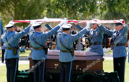 The Phoenix Police Department Honor Guard raises the flag over the casket of Phoenix Police Officer David Glasser, in Phoenix. Officer Glasser died May 19 a day after he was shot while responding to a call about a son stealing guns from his father