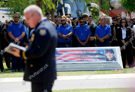 The coffin of Phoenix Police Officer David Glasser is seen in the background as a Phoenix Police Department Chaplin speaks to the family, in Phoenix. Officer Glasser died May 19, a day after he was shot while responding to a call about a son stealing guns from his father