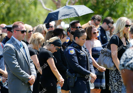 Police officers and friends attend the funeral for Phoenix Police Officer David Glasser, in Phoenix. Officer Glasser died May 19th a day after he was shot while responding to a call about a son stealing guns from his father. Glasser, a 12-year veteran, is survived by a wife and two children