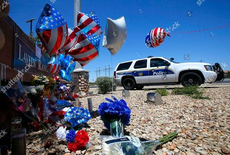 A Phoenix Police Department squad SUV parks next to a makeshift memorial to honor slain Phoenix Police Officer David Glasser near to where the officer was shot, in Laveen, Ariz. Officer Glasser was responding to a reported burglary on Wednesday in the Phoenix suburb, when an exchange of gunfire killed the police officer and the suspect