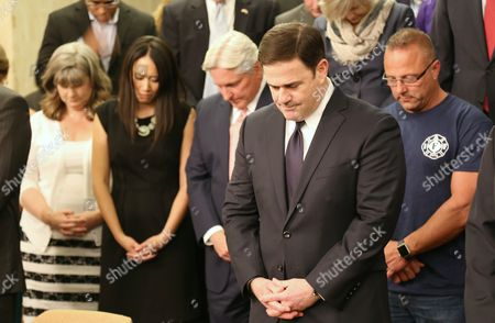 Arizona Gov. Doug Ducey, with other mourners, holds a moment of silence for Officer David Glasser, a Phoenix police offer fatally shot in the line of duty, at the state Capitol in Phoenix on
