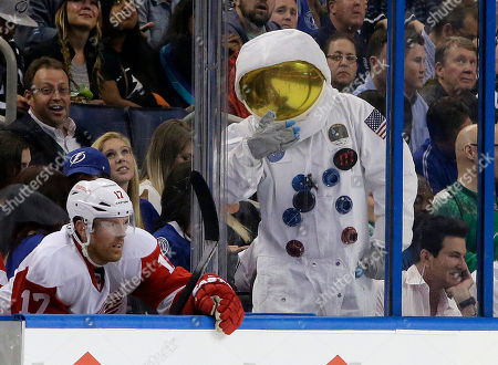 A Tampa Bay Lightning fan wearing an astronaut suit, taunts Detroit Red Wings center Brad Richards (17) during the third period of Game 5 in a first-round NHL hockey Stanley Cup playoff series, in Tampa, Fla