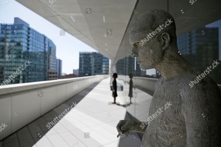 Sculptures by Marc Quinn, right, and Kiki Smith, left, are seen on a terrace during a preview of the newly expanded San Francisco Museum of Modern Art, in San Francisco. Designed in partnership with architecture firm Snøhetta, the expansion will more than double the museum's exhibition space. The museum opens on May 14. The sculpture at right is called Zombie Boy (City