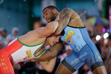 Iran's Pehman Yarahmadi, left, grapples with Jordan Burroughs of the United States in a 163-pound match during the Beat the Streets wrestling exhibition, in New York