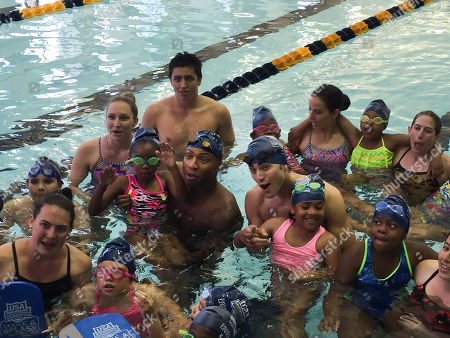 "Cullen Jones, Blake Michael Olympic gold medalist Cullen Jones, center-left, and Disney Channel star Blake Michael, center-right, pose with children and instructors who took part in a recent ""Make A Splash"" clinic at the Georgia Tech aquatic center in Atlanta. USA Swimming hopes celebrities will help spread the message that all kids need to learn how to swim"
