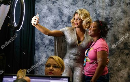 Stock Image of Katrina Kendrix, from Portland, Ore., poses for a selfie with drag queen reality television personality Tyra Sanchez at RuPaul's DragCon at the Los Angeles Convention Center in downtown Los Angeles. The rows of more than 230 vendors at DragCon hawking merchandise, from $20 T-shirts to $2,000 gowns, and the drag devotees purchasing it all is the latest example of the proliferation of fan conventions, the once geeky get-togethers that have morphed into a big business