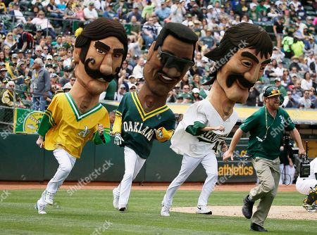 Oakland Athletics' figures from left, Rollie Fingers, Rickey Henderson and Dennis Eckersley take part in Hall of Fame race in the seventh inning of a baseball game against the New York Yankees, in Oakland, Calif