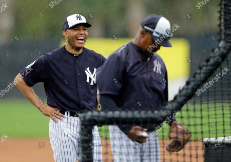 Former New York Yankees pitcher Mariano Rivera laughs as coach Willie Randolph throws batting practice before a spring training baseball game against the Atlanta Braves, in Tampa, Fla