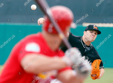 Miami Marlins starting pitcher David Phelps delivers a ball to St. Louis Cardinals' Matt Holliday during the first inning of an exhibition spring training baseball game, in Jupiter, Fla