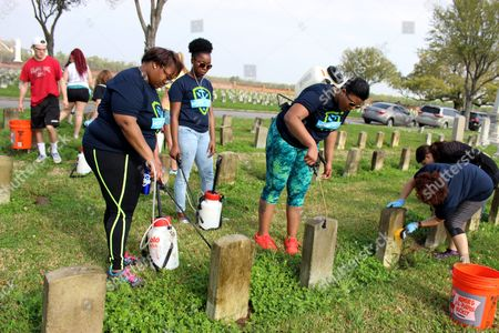 In a photo, Ohio State University students Willie Love, left, of Cincinnati, and Ashauna Mathews, of Canton, Ohio, spray a cleaning solution on gravestones at Chalmette National Cemetery in Chalmette, La. Between them is Jasmine Harris, of Cleveland. They were among about 50 Ohio State students working at the cemetery, as part of a nearly month-long project organized by the National Trust for Historic Preservation
