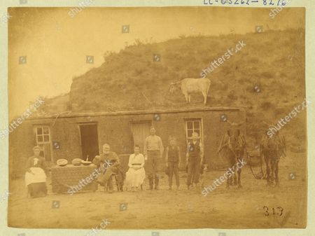 Sylvester Rawding family in front of their sod house, north of Sargent in Custer County, Nebraska, 1886. Photograph shows (from l. to r.) Emma (Leadbetter) Rawding, Sylvester W. Rawding, daughter Bessie, and sons Philip, William, and Harry, photographed by Solomon Devore Butcher 1856-1927