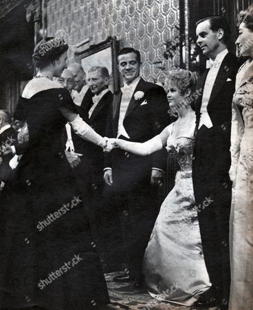 Brigitte Bardot meets Queen Elizabeth II of United Kingdom at the Royal Command Film Performance, London, 1956. Photograph in: Jours de France, France, November 10, 1956 (left to right: Dana Andrews, Brigitte Bardot, Ian Carmichael, Joan Crawford)
