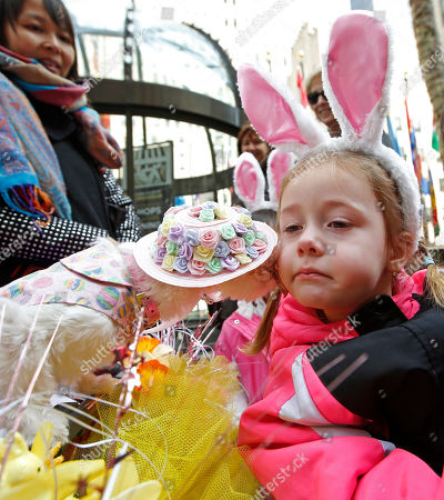 "A passerby watches as a dog named ""Coco Chanel,"" dressed in her Easter finery, plants a ""kids"" on the cheek of Ava Andersen, 4, of Latvia, during the annual Easter parade near St. Patrick's Cathedral, in New York"