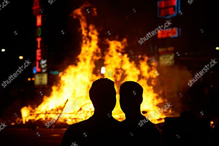 Las Vegas firefighters watch the controlled burn of the Life Cube, in Las Vegas. Artist Scott Cohen created the project, a 24-foot build-and-burn art installation, over the course of several weeks before burning it down