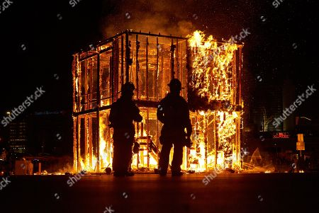 Las Vegas firefighters watch the controlled burn of the Life Cube, in Las Vegas. Artist Scott Cohen created the project, a build-and-burn art installation, over the course of several weeks before burning it down
