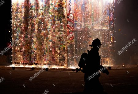 A Las Vegas firefighter watches the controlled burn of the Life Cube, in Las Vegas. Artist Scott Cohen created the project, a 24-foot build-and-burn art installation, over the course of several weeks before burning it down