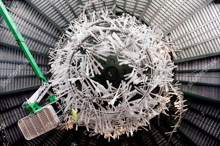 Anthony Churchill reaches to clean one of a thousand resin bats that hang as a sculpture at the home plate entrance to the Seattle Mariners' ballpark, in Seattle. Workers expect to take about three days to clean the sculpture that reaches up to about 50-feet above the entryway. The team opens the home portion of their season against the Oakland Athletics on Friday