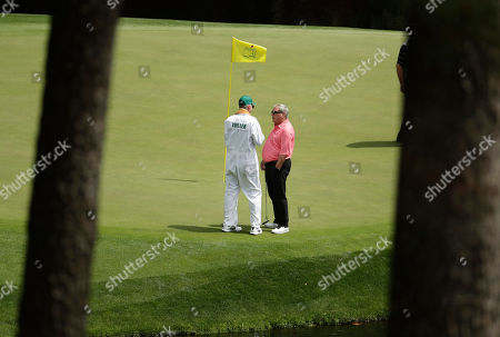 Fuzzy Zoeller speaks to a caddie on the eighth hole during the par three competition at the Masters golf tournament, in Augusta, Ga