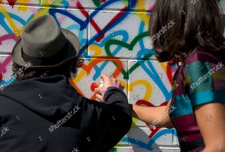 Michelle Obama, Mr Brainwash First lady Michelle Obama and Mr Brainwash spray-paint together as part of a live painting of a Let Girls Learn mural at Union Market in Washington, in celebrations of Let Girls Learn and International Women's Day