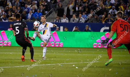 Mike Magee, Andrew Dykstra, Sean Franklin Los Angeles Galaxy forward Mike Magee, center, kicks the ball past D.C. United goalkeeper Andrew Dykstra, right, for a goal as defender Sean Franklin defends during the second half of an Major League Soccer match, in Carson, Calif. The Galaxy won 4-1
