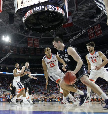 Butler forward Andrew Chrabascz (45) moves the ball against Virginia guard Malcolm Brogdon (15) during the second half of a second-round men's college basketball game in the NCAA Tournament, in Raleigh, N.C. Virginia won 77-69
