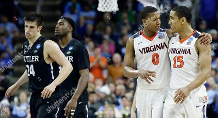 Virginia guard Devon Hall (0) speaks with Virginia guard Malcolm Brogdon (15) after the second half of a second-round men's college basketball game in the NCAA Tournament against Butler, in Raleigh, N.C. Virginia won 77-69