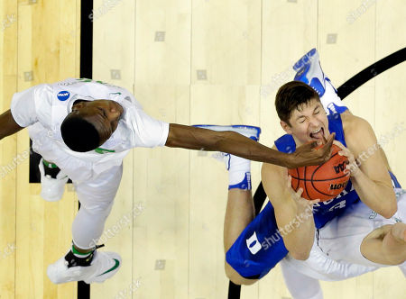 Oregon forward Chris Boucher, left, fouls Duke guard Grayson Allen during the second half of an NCAA college basketball game in the regional semifinals of the NCAA Tournament, in Anaheim, Calif